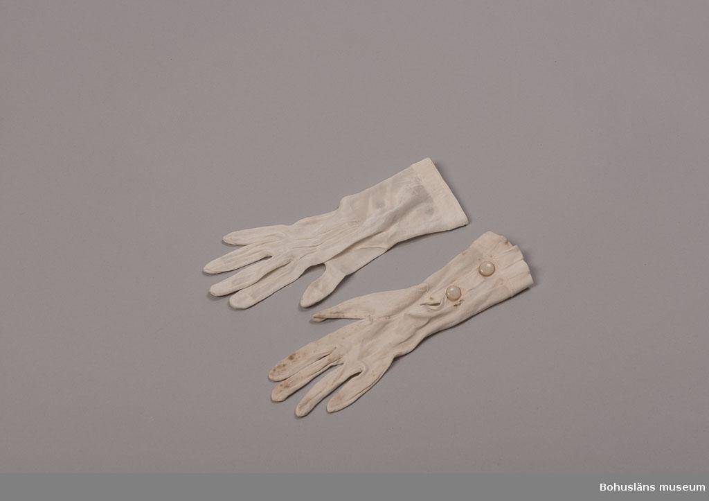 Ett par vita silkevantar med tre dekorativa sömmar på ovansidan till brudklädsel. På insidan knäppning med två tryckknappar med ovansida av celluloid, avsett att lika ben eller elfenben. Färgförändringar har skett på materialet. På högra handsken skada vid knäppningen. Uppgifter om brukaren, bröllopet och brudklädseln se UM026644
