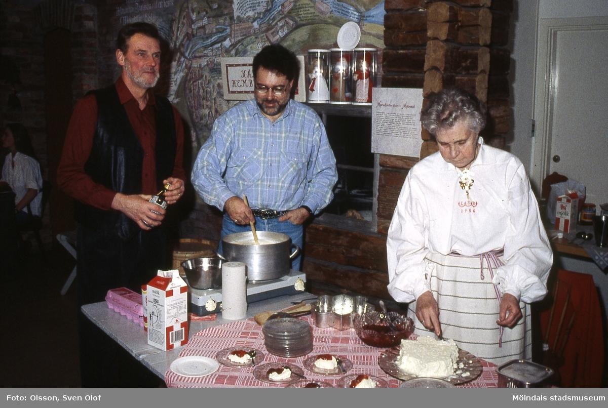 Kållereds Hembygdsgille serverar äggost på Mölndals museums julmarknad den 5/12 1993. Från vänster ses Berny Gustafsson, Staffan Bjerrhede och Lily Edvardsson som bär Kålleredsdräkten. Kv 16:21.