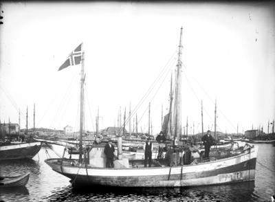 Eldre fiskebåt (fiskekutter) med mannskap om bord og et norsk flagg til topps en akter mast.