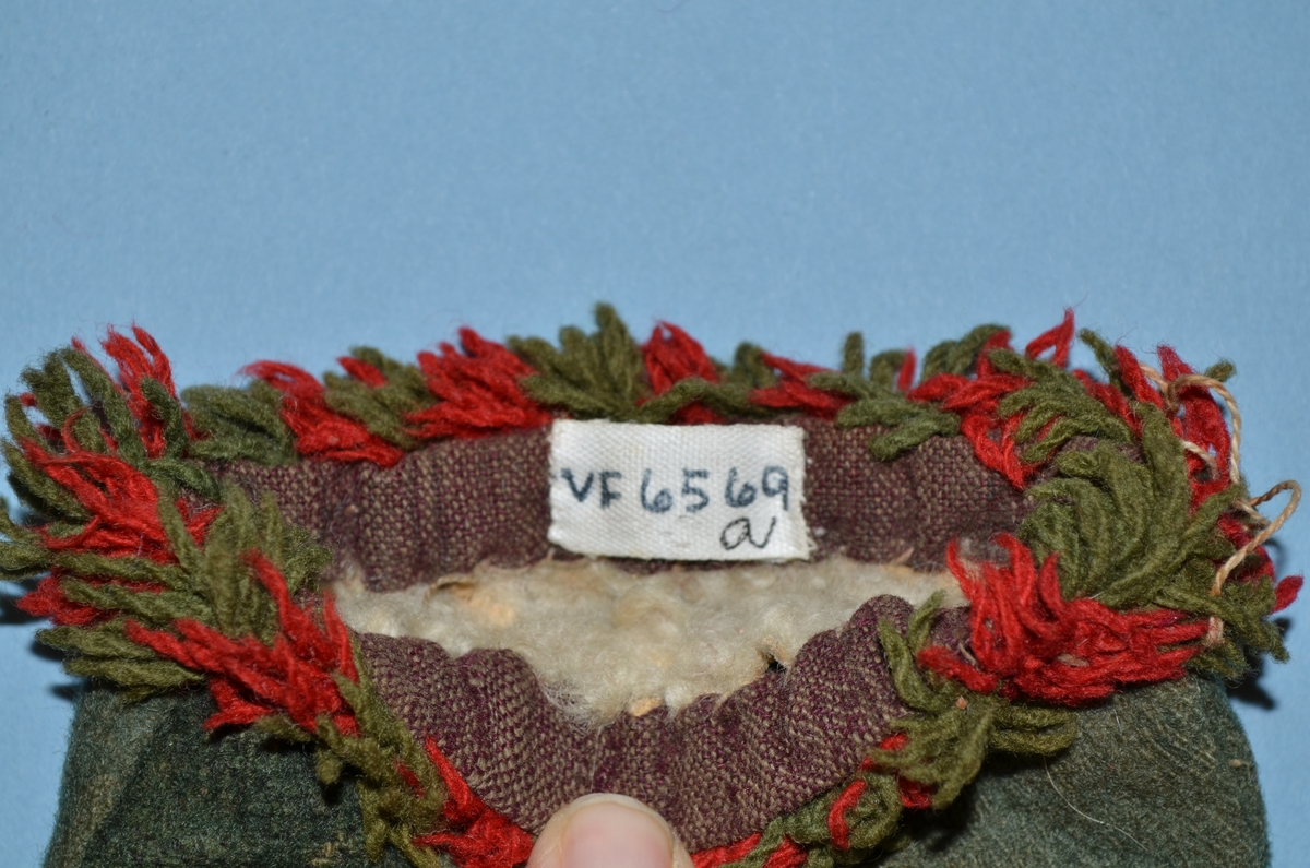 Vott (a+b), kypertvevd ull, grønn. Forside tommel mørkere grønn og stampet. Håndsydd. Rød og grønn frynsebord i kantene, festet på kant av toskaft bomull (brun og beige). Fôr i lammeskinn.