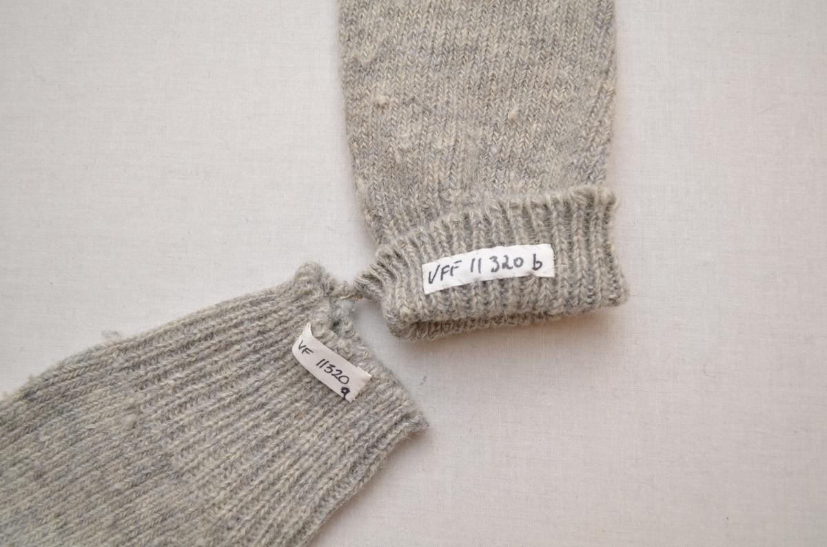 Lange strømper (a+b), strikket i koksgrått ullgarn. Ribbestrikka legg, 2 rette og 2 vrange. Stoppet under på hæl og tå med hvitt og grått garn