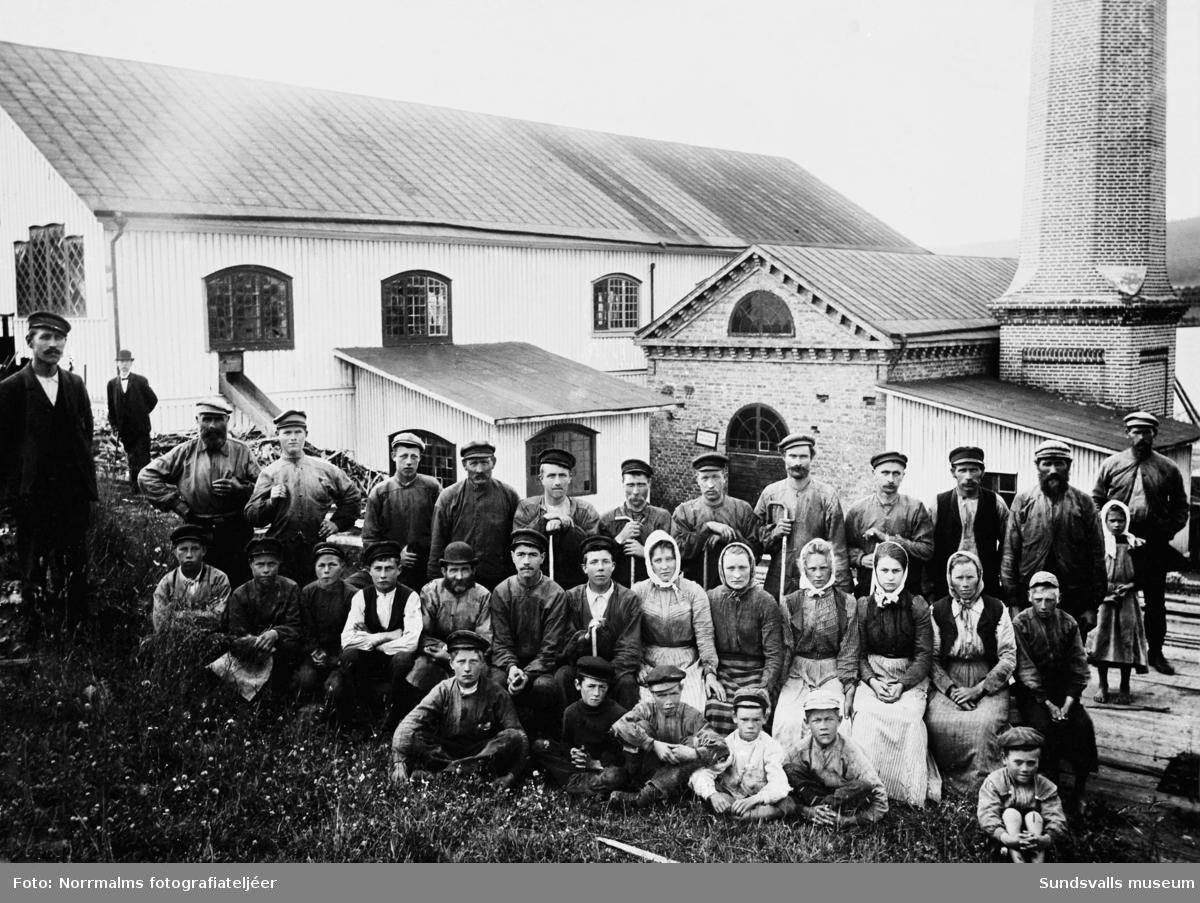Gruppbild med arbetare på Gustafshamns sågverk, Alnö. Mannen i plommonstop i bakgrunden kan eventuellt vara ägaren Gustaf Andersen.