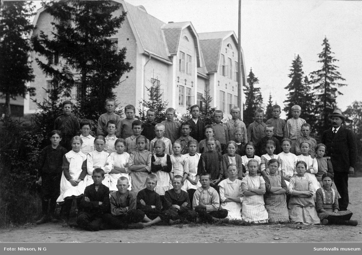 Hovids skola med lärare och elever framför byggnaden.