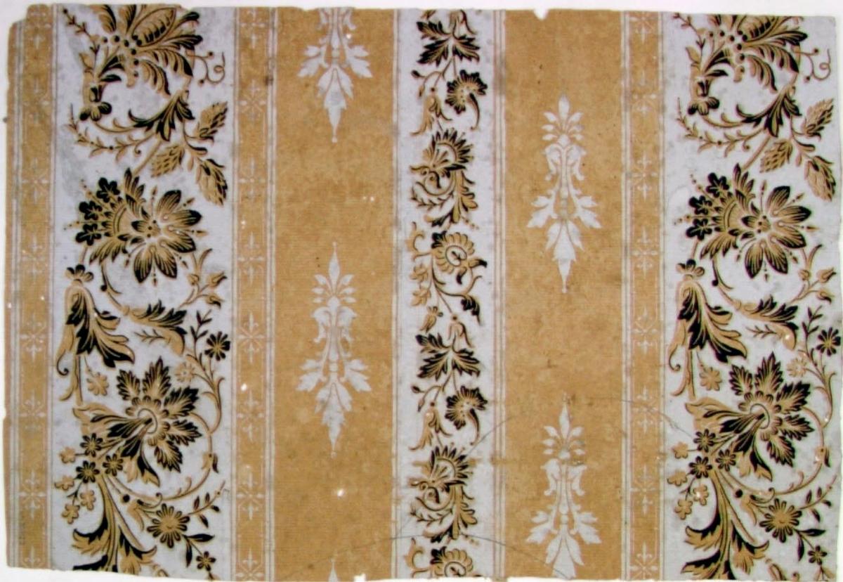 /Tapet uppsatt direkt på timmervägg/  Lodrätt randmönster  omväxlande dekorerat med franska liljan respektive med en fantasifull slingrande barockblomma. Tryck i svart och ljusgrått på ofärgat papper. Stilblandning av nyrenässans och nybarock.
