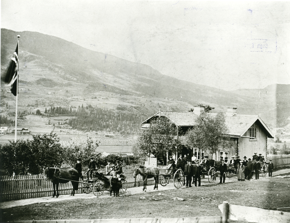 Reisefølge ved Tamburgarden i Bagn, då Ole O. Bang, som sit i den fremste vogna, var på veg til Amerika.