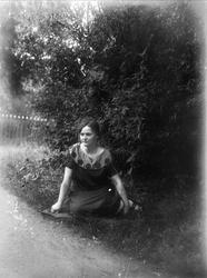 Elsa Alström från Fröslunda sitter i trädgården, Altuna sock