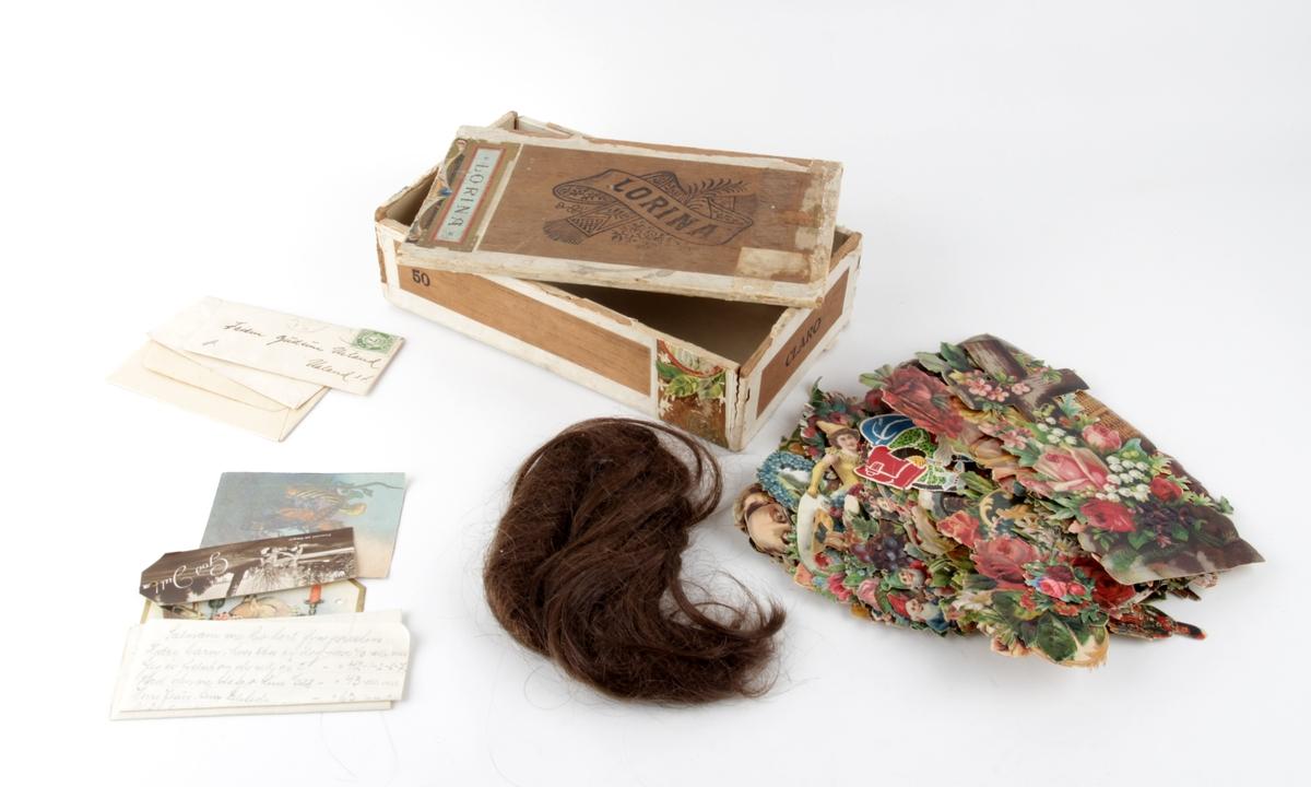Sigareske som inneholder glansbilder, hårlokk, visittkort og diverse lapper.