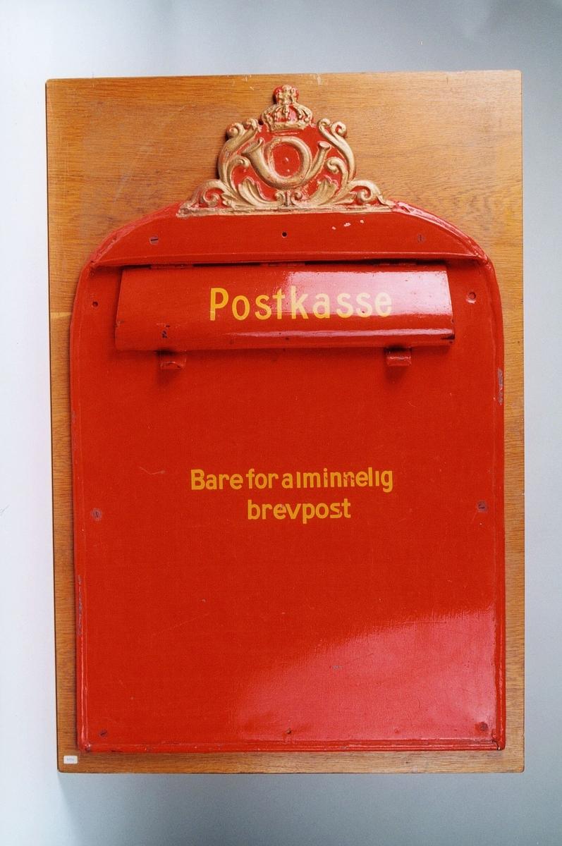 Postkasseskilt/innkast i metall som er rødmalt. Postinnkastet er montert på treplate og har gullfarget posthornemblem og gul skrift.