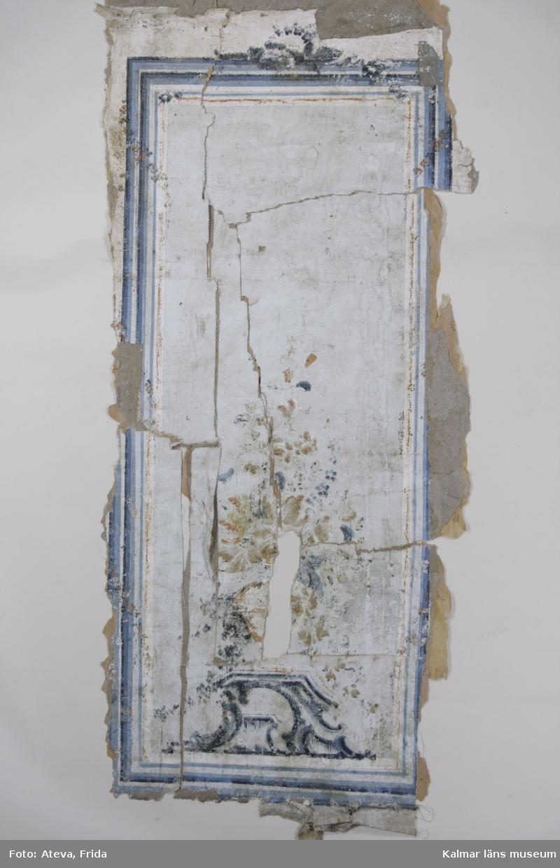 KLM 43843. Tapet av papper. 44 st tapetbitar. Överst tryckt tapet med rött och vitt blom- och bladmönster på ofärgat papper. Under detta ett lager med tryck i vitt och rött, troligen lodräta fältindelningar. Tryckt på ofärgat papper. Under detta en schablonmålning med lila botten och schabloner i mörkblått med stiliserade blommor och blad. På baksidan av bitarna målad tapet på väv med vit eller grå botten och fältindelningar i cinnober, vitt och blått. På några av bitarna syns en målad blomsteruppsättning i grönt, svart, blått, cinnober och gult. På några bitar är en blomsterslinga målad längs fältindelningarna. På ett antal bitar syns underliggande lager med stänktapet med blå botten och stänk i vitt och svart. Målningen på väv har troligen suttit utåt i rummet och sedan blivit vänd när schablonmålningen skulle målas. Vissa av bitarna går att para ihop och ger då en bättre bild av målningens utseende. En av bitarna har annan målning med streck i blått, cinnober och grönt, strecken har troligen fungerat som fältavdelare. I fältet en målad stiliserad blomma i vitt, grönt, blått och cinnober. Denna målning har suttit under den ovan beskrivna schablonmålningen.