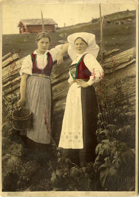Kolorert fotografi av to kvinner med Hardangerdrakt foran et gjerde på seteren. 1908.