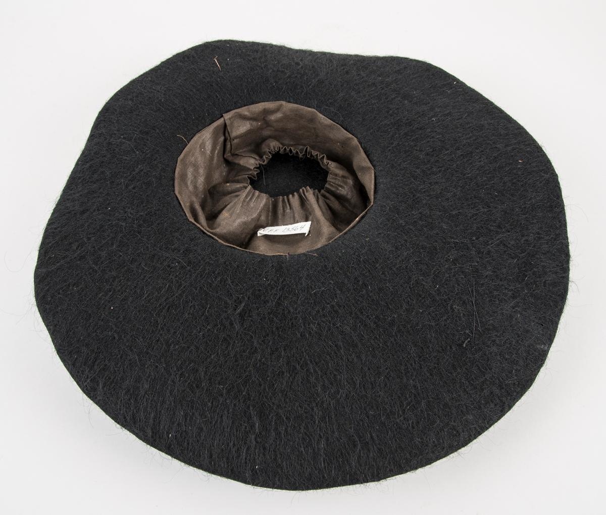 """Hatt, svart bredbremma filthatt. Svarte fløyelsband, pynta med metall """"nål"""". Fóra inne med brunt bomullstøy."""