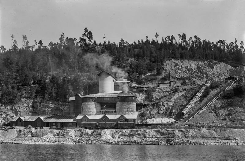 Svart-hvitt bilde av kalkbrenneri sett fra Mjøsa: store, runde kalkovner med tak og kalkbrudd i bakgrunnen.