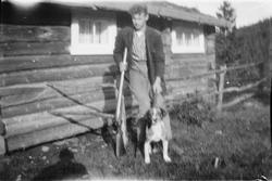 Mann med våper og hund utenfor hytte. Harejakt?
