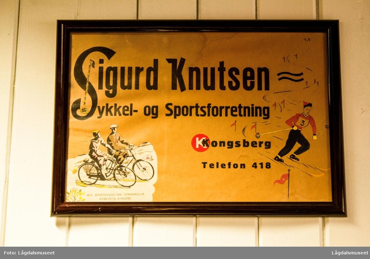 En innrammet reklameplakat som viser bedriftens navn og enkle illustrasjoner av ulike idrettsgrener.