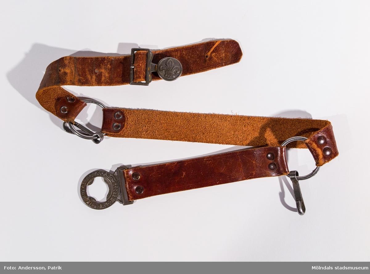 """Scoutskärp i tre delar, av brunt skinn, som hålls ihop av två metallringar fastsatta med nitar samt knäppe. I ringarna hänger var sin karbinhake. Metallknäppet består dels av en scoutsymbol (fransk lilja) samt en ring med gjuten text """"BOY SCOUTS ALLTID REDO"""". Fyra hål finns för att reglera faststängning med. Skärpet har använts av givarens broder under dennes nyingperiod från 8 till 14 års ålder."""