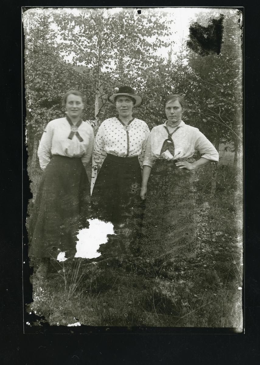 Portrett i helfigur av 3 kvinner som står ute, foran noen bjørketrær. Alle er kledd i mørke, side skjørt og ulike, lyse bluser.
