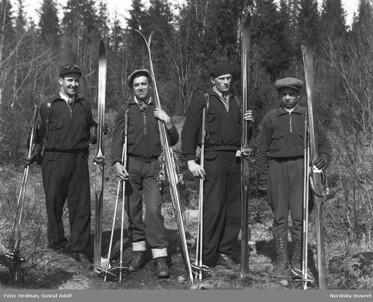 Fyra män med skidor och stavar.