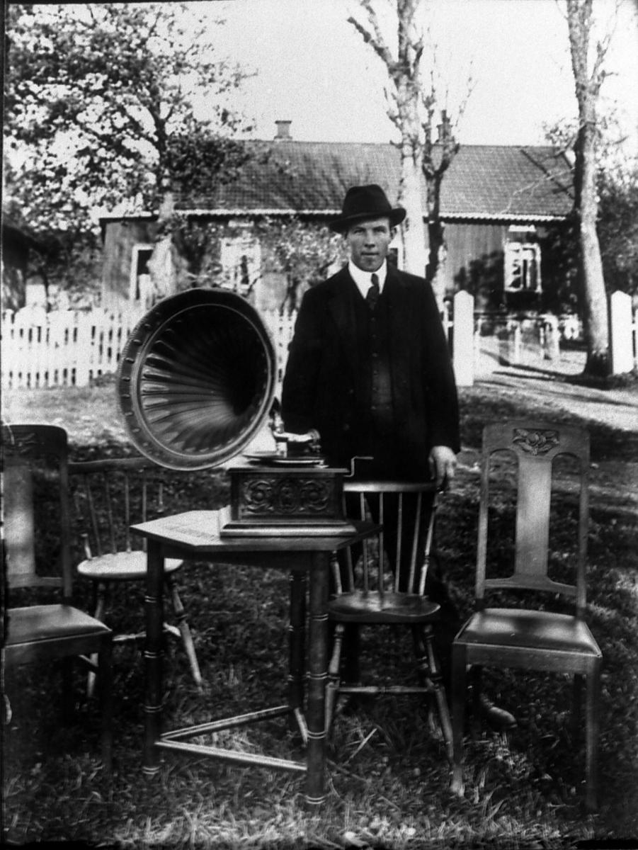 Herbert Johansson Örbytorp V-Kleva. Han var dräng hos Anna Persson i Ögården. Grammonfonen hade Annas man Gustav köpt på auktion i Änga. Fotot taget i Ögården.