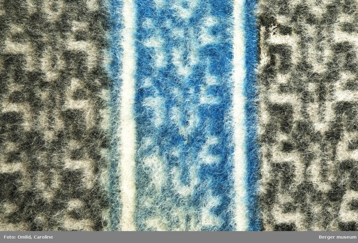 Teppe med geometrisk strukturmønster i mørk grått på lysere bakgrunn. Tverrgående blå bord med samme mønster.