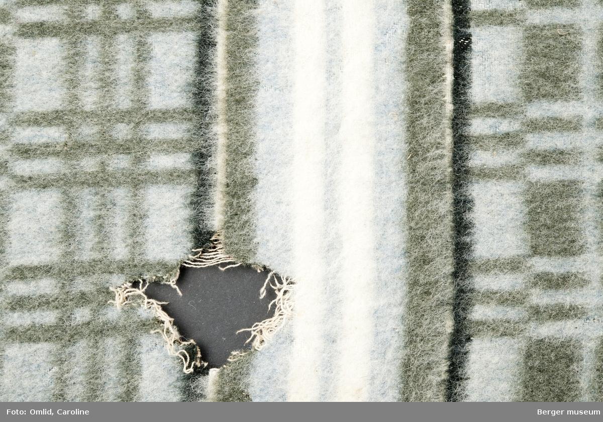 En prøve. Blå bunn, grå striper i et rutemønster. Borden er en bred stripe i midten i lengderetning og tre smale striper på begge sider; svart-hvit-grå-blå-hvit-blå-gjentatt tilbake. Stort hull midt på fra møllangrep.
