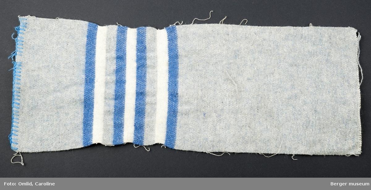 En prøve. Ensfarget grå med stripebord; blå-hvit-grå-blå-hvitblå-grå-hvit-blå.  Noe skitten.