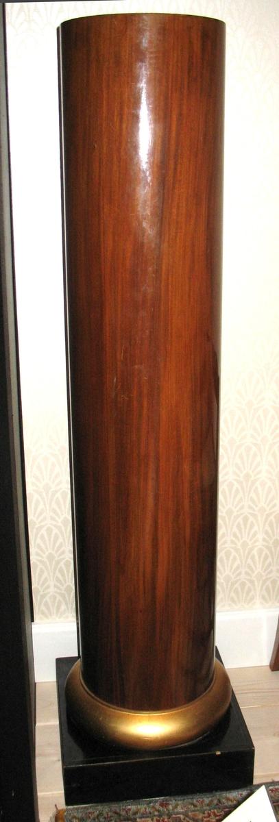 Kat.kort: Piedestal, mahognyfanér. Slät kolonn med förgylld fot. Underlägg för kruka i läder.