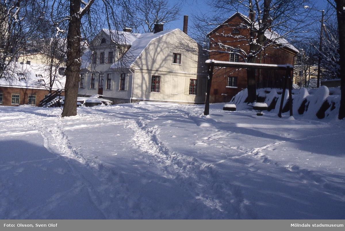 Kvarnbygården och kvarnstenarna i snö. Vy från Kvarnbyparken mot hembygdsgården vid Royens gata 8 i Mölndals Kvarnby, år 1999.