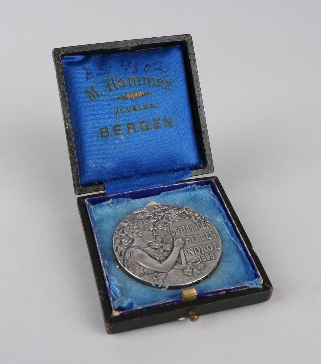 Sølvmedalje fra utstillingen Bergen, Norge 1898. Kvinne omringet av bladkrans, bakside tre fugler som flyr, samt tekst. Ligger i liten eske av papp.