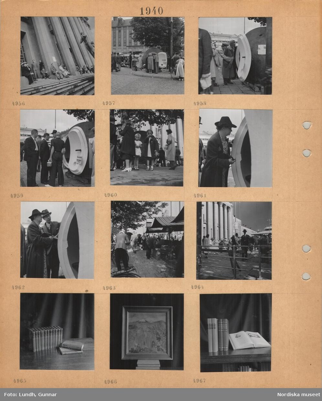 Motiv: Hötorget, Stockholm, konserthuset, personer på trappan, några män och kvinnor tittar in i en stor rund kula med öppen dörr, ett skyddsrum, i bakgrunden Pub-huset, salustånd, böcker uppställda på ett bord, inramad målning uppställd på ett bord.