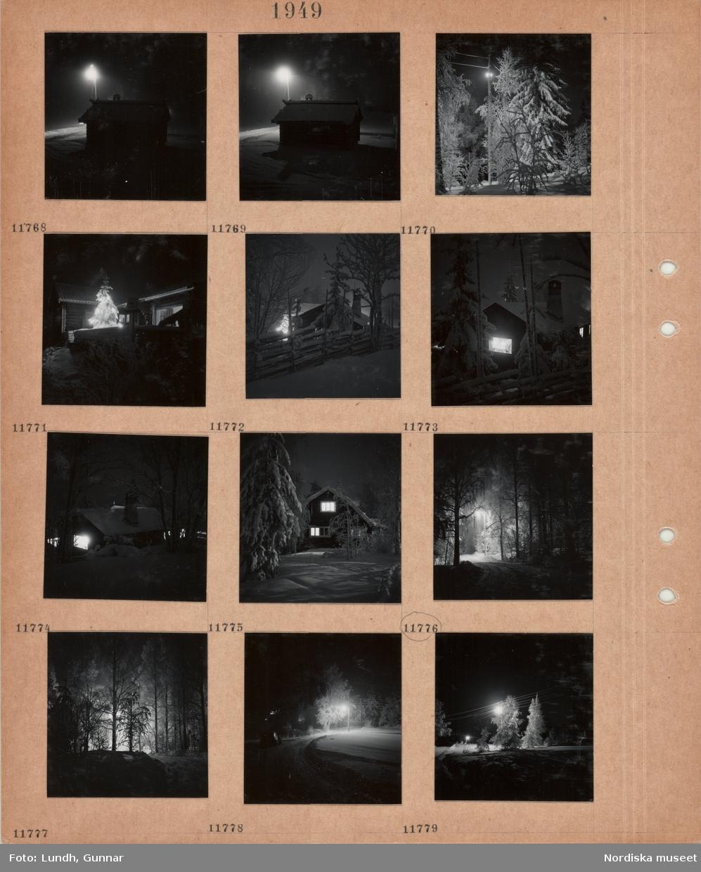 Motiv: Tällberg, liten timmerbyggnad i snö i kvällsmörker med tänd gatubelysning, höga snöiga träd, tänd gatlykta, snöig julgran med tänd belysning på husveranda, trägärdsgård, skorsten, upplysta fönster, väg mellan höga träd, tänd gatubelysning, bil på snöig väg i mörker.