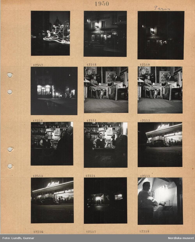 Motiv: Paris, kyrkan Sacre Coeur i mörk silhuett, ljuseffekter i bilden, ingång till restaurang, kväll, gathörn, upplysta fönster, en kvinna med hund och en man i tavelaffär(?), värmekamin, man vid bardisk, hyllor med flaskor och glas, reklamskyltar, gäster, skålande personer vid bardisk, parkerad bil framför ingång till restaurang med neonskylt, stora fönster, mörk gata, personer står vid upplyst enkel servering under markis, en man tillreder mat.