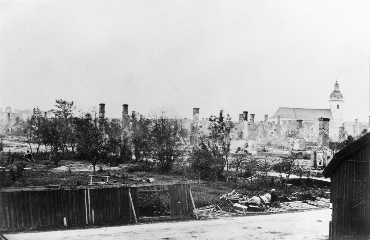 Efter Gävle brand 1869. Utsikt från hörnet av Norra Kungsgatan och Staketgatan. Planket i förgrunden innesluter läroverkstomten.
