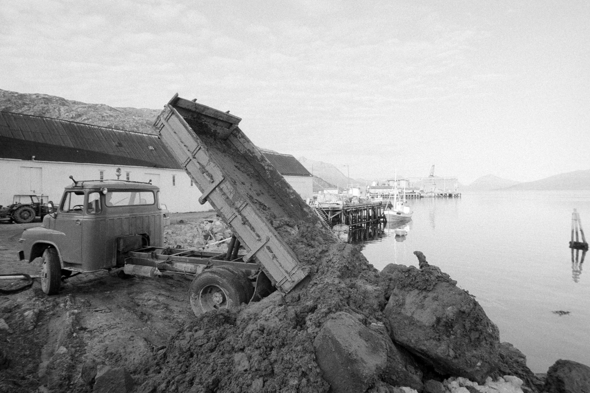 Lastebil tipper masser ut i sjøen i forbindelse med anleggsarbeid i Lødingen.