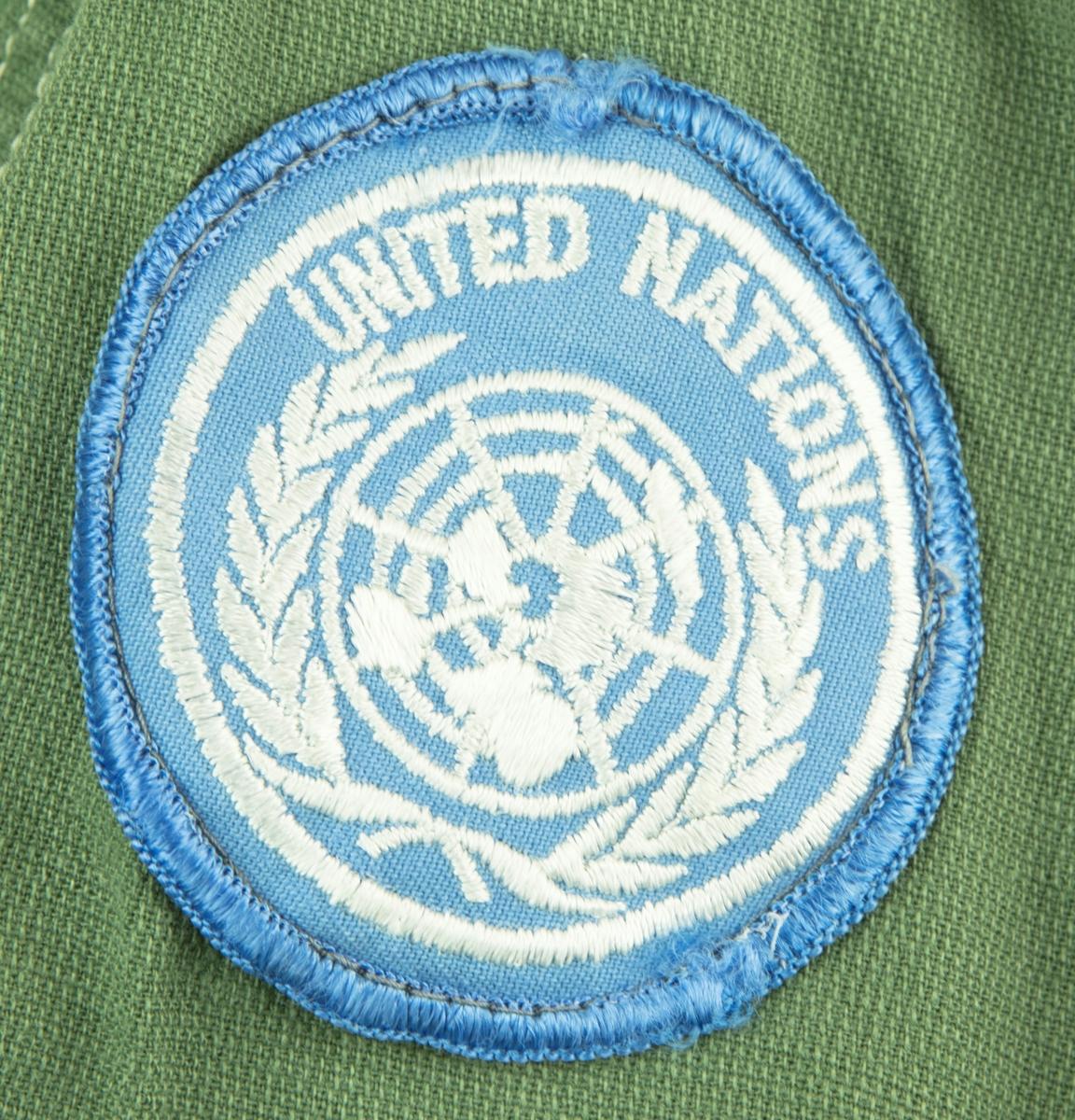 """Skjorta i ljus militärgrön, brukad vid FN-tjänst. Två bröstfickor fram med knäppning. Knäppning fram med fyra knappar. Slejf på vardera axel för axelklaffhylsor. På vänster axel (framifrån) sitter ett ljusblått tygmärke med FN logga, på höger axel sitter ett tygmärke med Svensk vapensköld och texten """"SWEDEN"""" i gult. Storlek XL."""