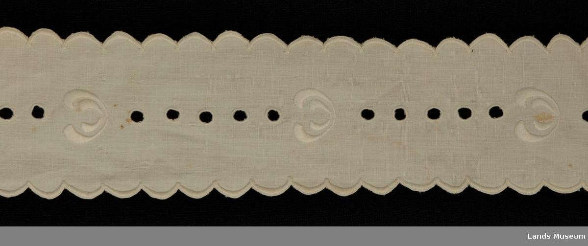 Til å ha rundt ostestykke. Brodert på hvitt linstoff med hvitt bordergarn i engelsk søm, gjennom hullene. Tunger brodert rundt hele. Ene endestykket er rett, det andre er avrundet.