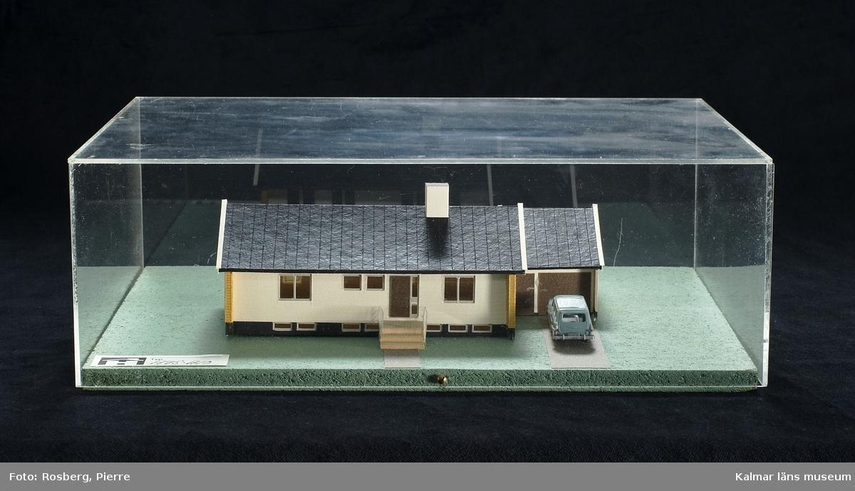 KLM 28685:1 Husmodell av trä mm. Modell i skala 1:100 av ett monteringsfärdigt småhus från Hultsfredshus med beteckningen A95-A10. Naturliga färger. Monterat på tunn grönmålad spånplatta och täckt med en huv av plexiglas.