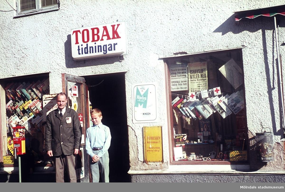 En man och en pojke utanför tobaksaffären i huset Kvarnbygatan 43 vid Gamla torget i Mölndal, 1970-tal. Kv 45:18.