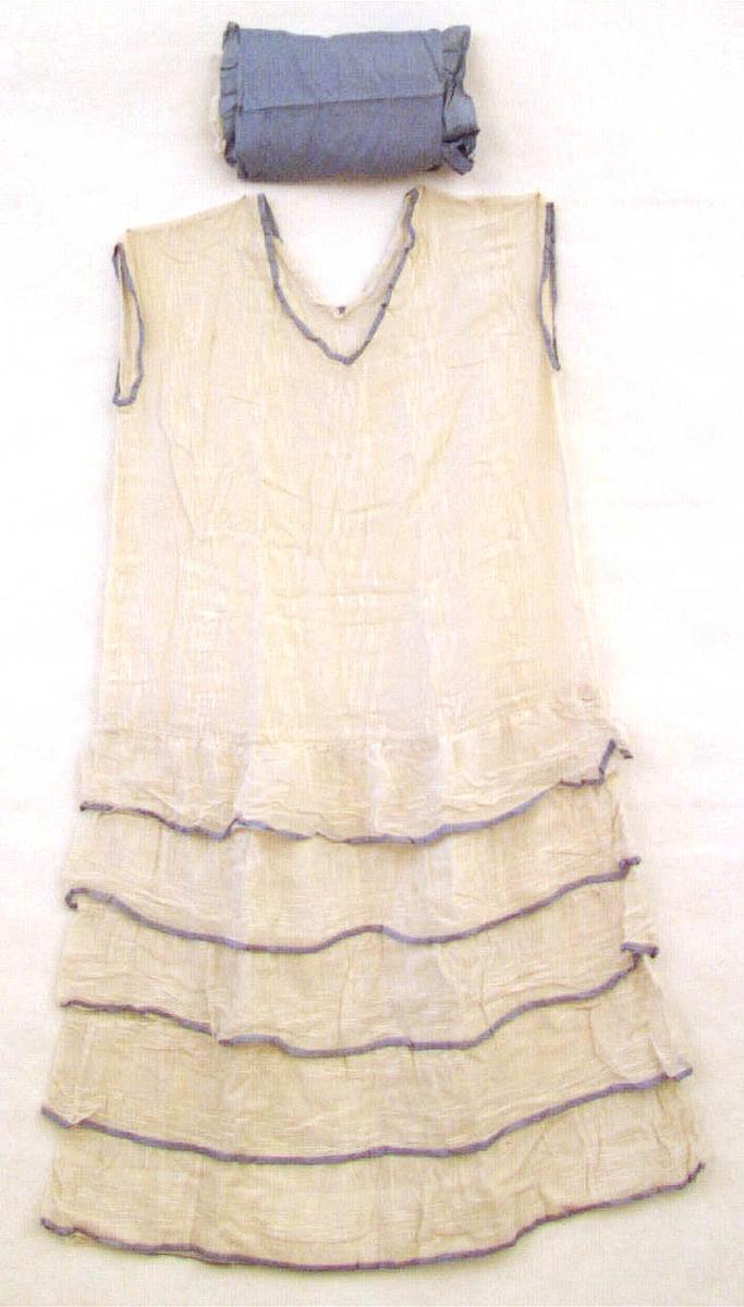 Klänning av vit bomullstyg. V-ringad och utan ärmar. Långt liv och kort, vådförsedd kjoldel. Det vita tyget, v-ringningen och ärmhålor kantade med blå band likaså kjolens våder. Hemsydd.