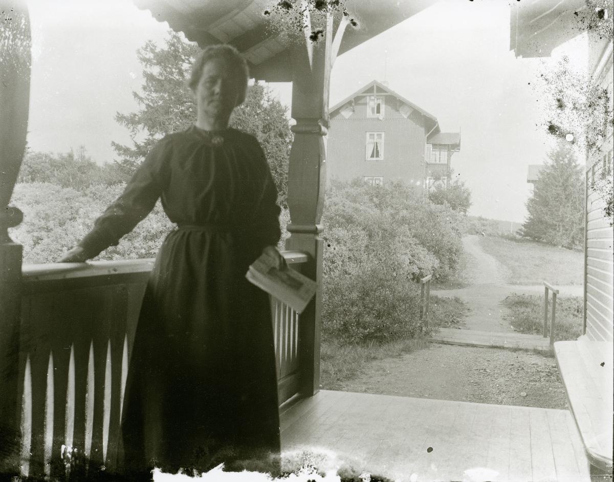 Kvinne som står på en veranda med ei bok i handa.