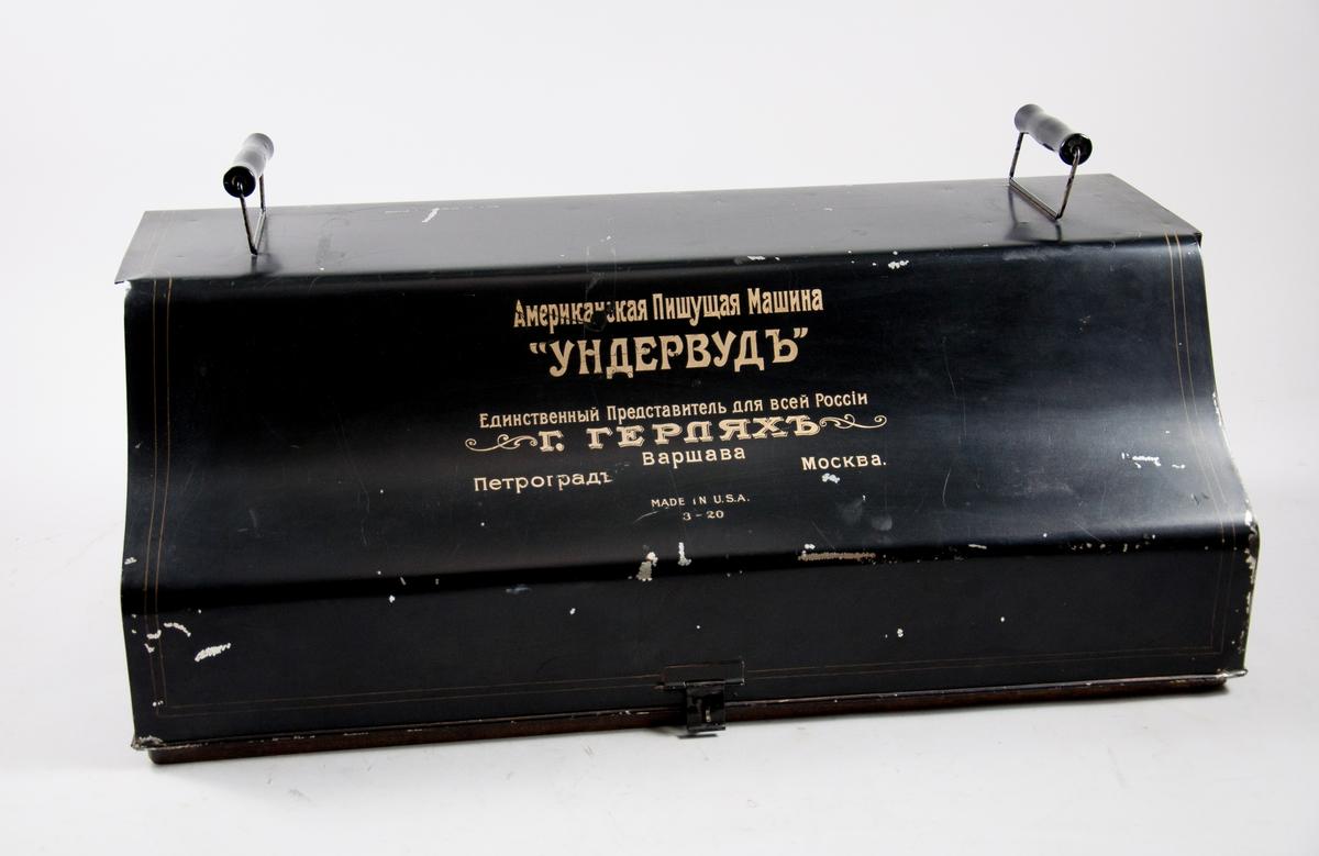 Skrivmaskin Underwood Standard Typewriter No. 3, 20 inch bredd. Märkt med adress för Underwoods återförsäljare i Petrograd, Moskva och Warszawa.  Svensk teckenuppsättning, med å, ä och ö. Monterad på träplatta, med huv av plåt.