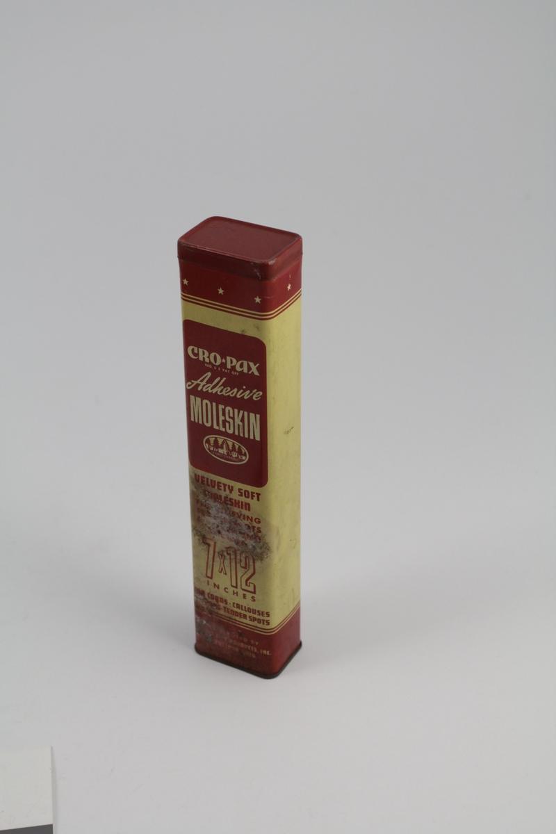 Rektangulær boks med lokk - åpning i den ene kortsiden. Bruksanvisning på boksen - inneholdt mulvarpskinn til bruk ved gnagsår.