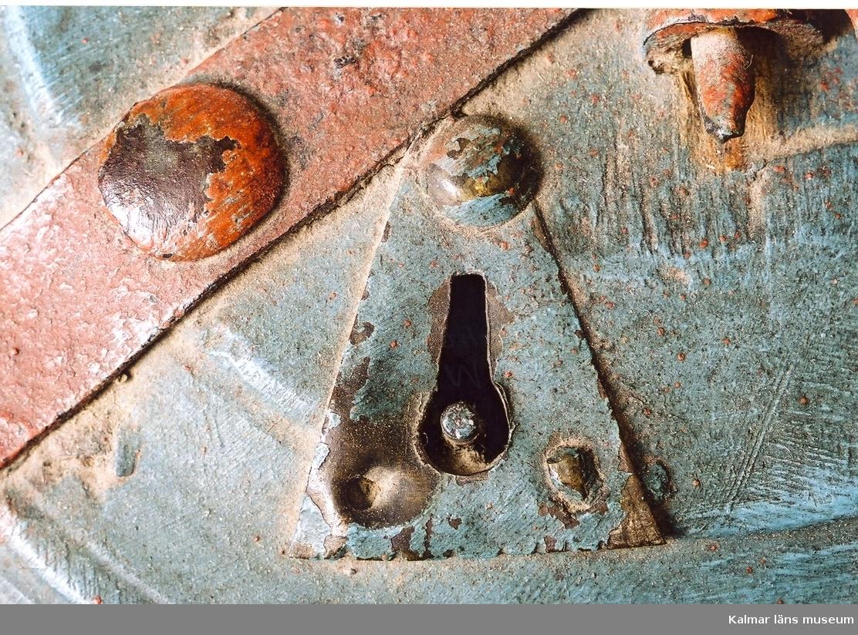 KLM 5672.  Äska, rund, diameter 32 cm. höjd 15 cm. Svarvad i trä, bok, samt försedd med järnbeslag och överst ett handtag av järn. Vridlock med lås märkt: C L D 1803. Blåmålad, beslagen röda.   Påklistrad etikett med text: knäpp-äska, westgöta landskapsmål i stället för Knäpp-äsk. Deruti buros af Gårdfarihandlare nålar, sy-ringar, tråd och dylikt. Gåva till fornm. fören:g af Apothekaren Hj. Lind i Borås genom J.A. Södermark.