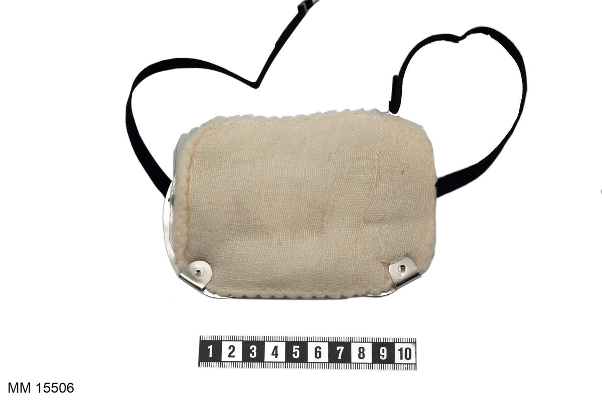 Munskydd bestående av stomme i aluminiumplåt med svart resårband, på denna fästes ett filter av bomull och gasväv, förvaras i fodral av röd plast. På plåtstommen instansat: Martindale Protective Mask ' For Nuisance Dusts Only', Brit. Pat. 1075346 & Others, Martindale Protection L T D. London N. W. 10.