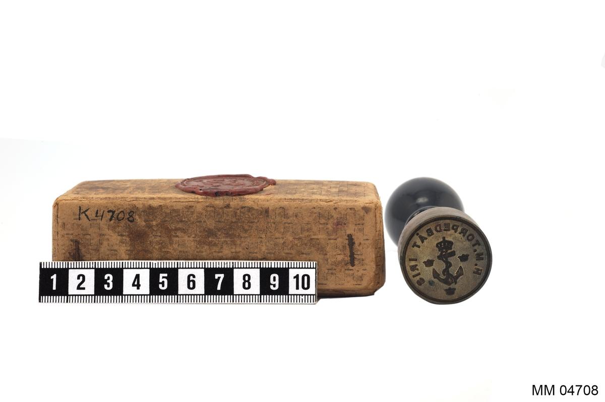 Sigill av mässing. Cylindriskt med svarvat handtag av svartpolerat trä. Text: H.M. Torpedbåt Iris, dessutom ankare med kunglig krona, omgiven av tre mindre kronor. Förvaras i pappask med sigill i lack.