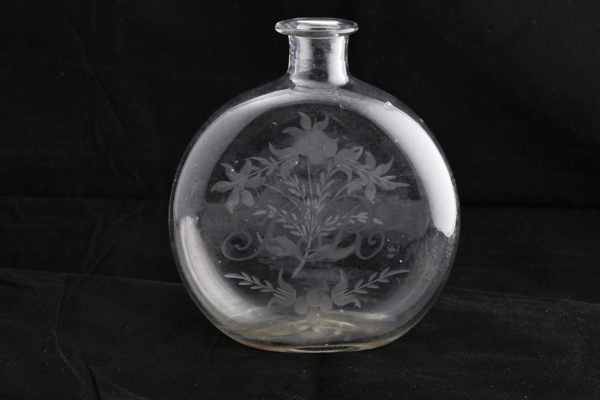 Rund, flattrykt flaske som så vidt kan stå, hals med bred, flat ring og kork. På siden er gravert blomster og initialer. Gravyren er meget dyktig utført, med rene kanter.