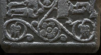 Detalj fra en middelaldergravstein; en flott uthugget fembladet blomst med bladranker rundt.. Foto/Photo