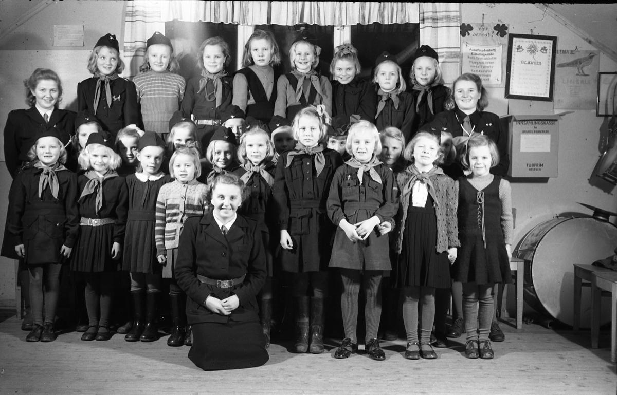 """Speiderpiker med ledere, Lena desember 1948.  Foran fra venstre: Kari Fodstad, Berit Fodstad, Anne Marie Berg, Else Lise Bøe, Anne Lise Aass, Elisabeth Kraby, Karin Stangstuen, Synnøve Haavi, Turid Haavi. Midtrekken fra venstre: Eivor Haavi (leder), Irene Iversen, Mary Iversen, Erna Pedersen, Solveig Dahl, Grethe Trillerud, Mina Bjerke (leder), Solveig Jørstad, Siri Lieng eller Sonja Bakkeli (?), Liv Lauritsen, Synnøve Dahl, Reidun Rindal, Gerd Bojsen Aamodt (leder). Bakerst fra venstre: Signe Ragnhild Fodstad, Reidun Olsen, Astrid Sukkestad, Elsa Henriksen, Ingegjerd Røise, Liv Hagen, Vigdis Margaret Rødset, Lillian Tandsæther. Bildet er tatt på """"Harmonien"""" på Alfstad søndre."""