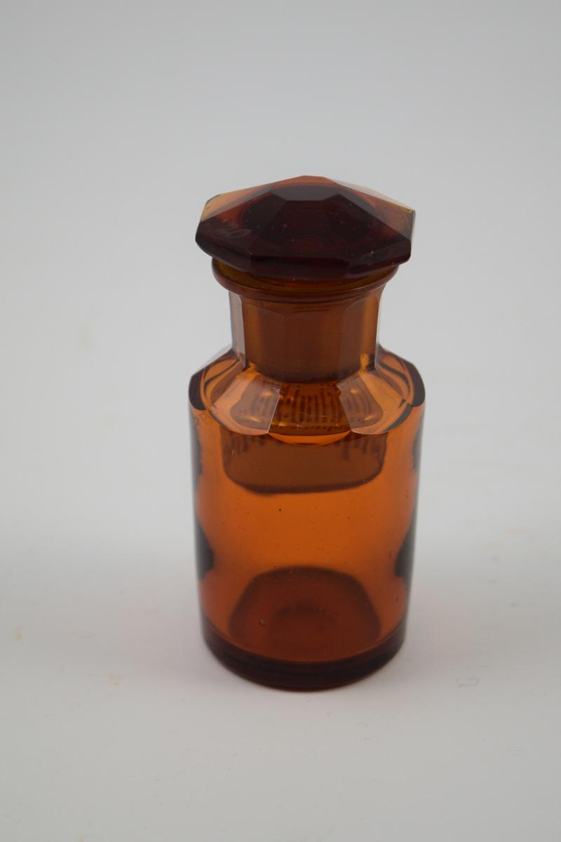 Brun glasskrukke med glasspropp. Etikett hvit med rød skrift. 2 kors, det vil si meget giftig. Bitartr. suprarenic: til medisinsk bruk, veldig giftig.