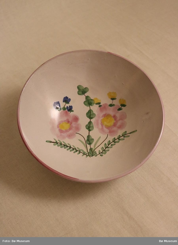 Håndmala blomstermotiv og rosa rand langs munningen.