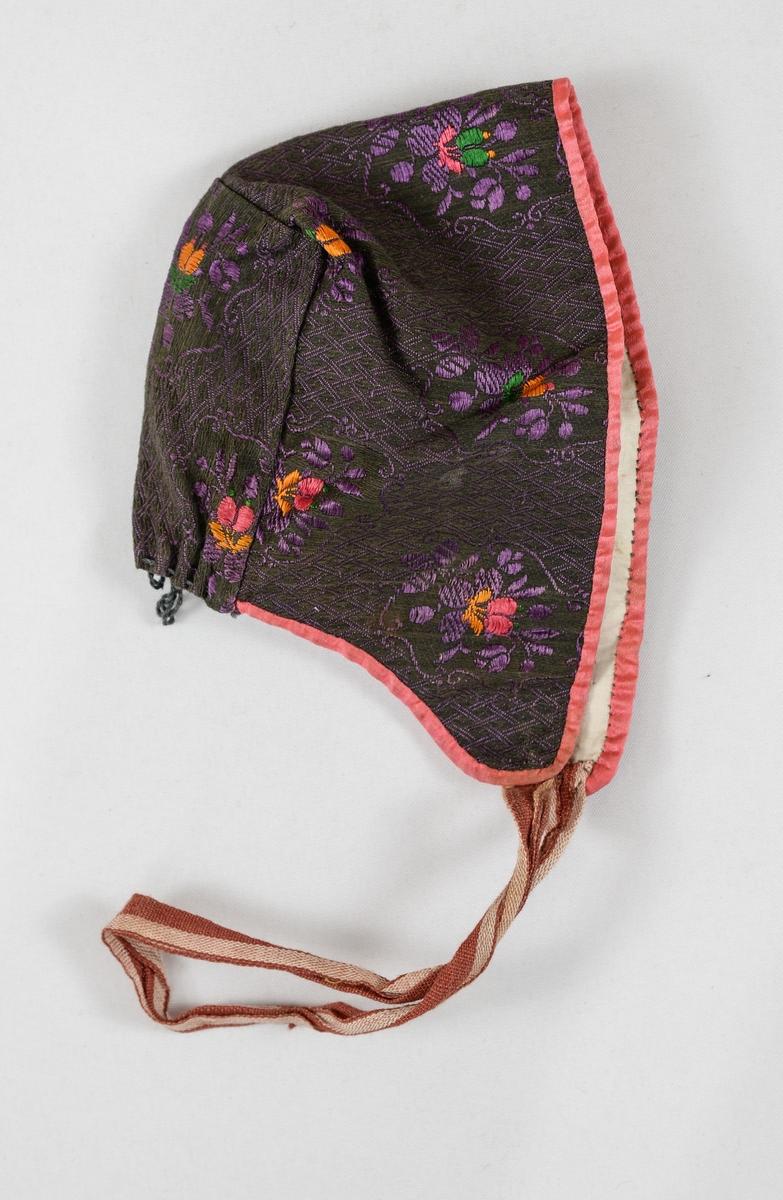 Dåpslue. pullue, i brun og lilla brosjert damask. Kanta rundt med rosa silke, bortsett frå eit stykke på 6 cm midt bak som er samanrynka. Fóra med bomull. Eitt vevd knyteband i brunt og beige.